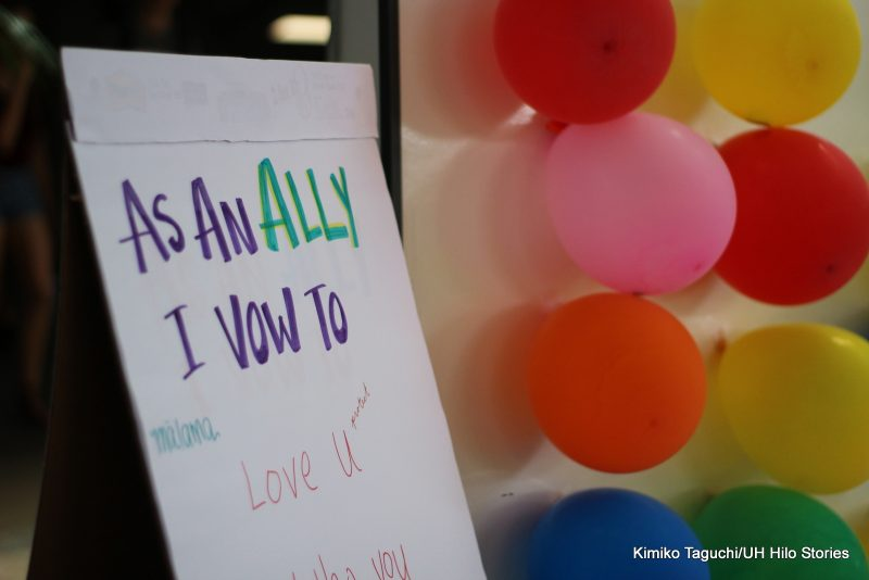 "Sign at the event with words, ""As An Ally I Vow To... Love U...."" Colorful balloons at right of sign."