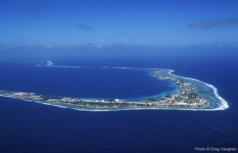 Majuro Atoll, horseshoe shape in deep blue water, white ocean break on right coast.