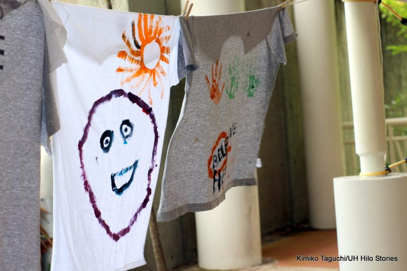 Painted t-shirt with smiley face and sun.