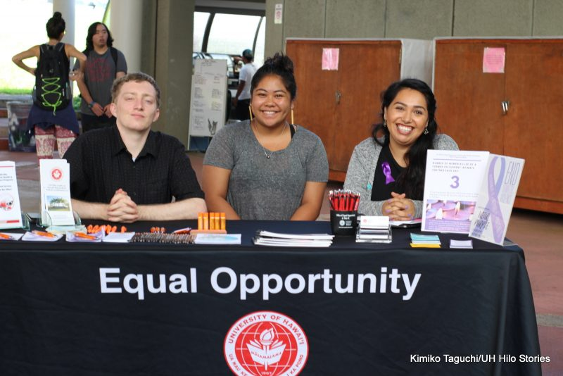"Three staffers at table labeled ""Equal Opportunity."""