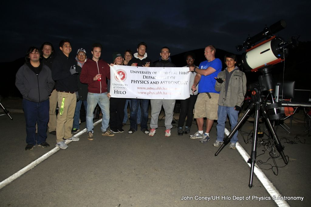 "Group stands for a photo with sign, ""UH Hilo Department of Physics and Astronomy."""
