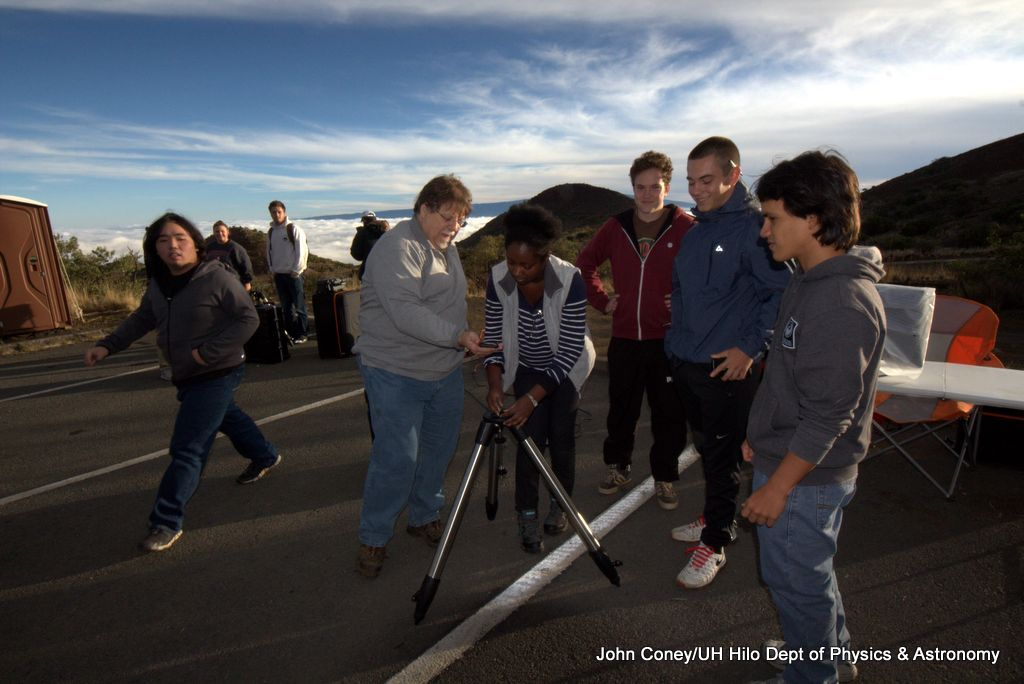 Professor guides students as they set up telescope.