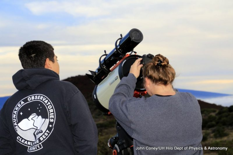 Students check the telescope lens.