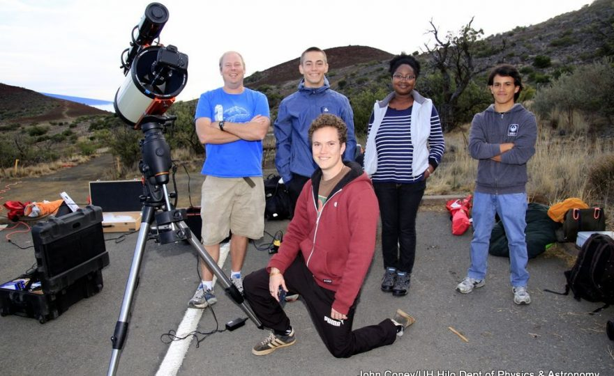 Group standing next to telescope.