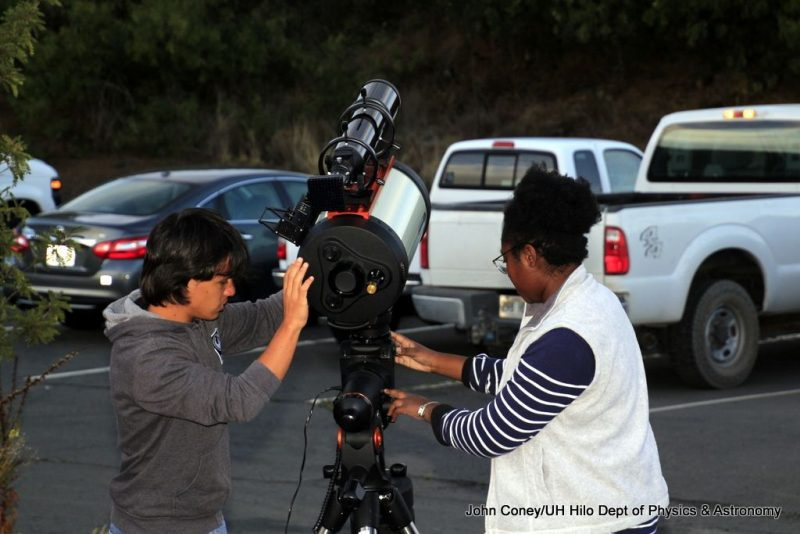 Students double check set up of telescope.