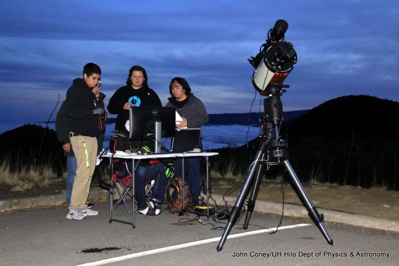 Students checking laptop as night falls.