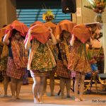 Female dancers in traditional Philippine attire, scarves over heads.