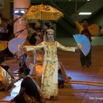 Dancers, female lead in yellow with umbrella.