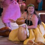 Solo woman doing traditional Hawaiian chant with gourd.