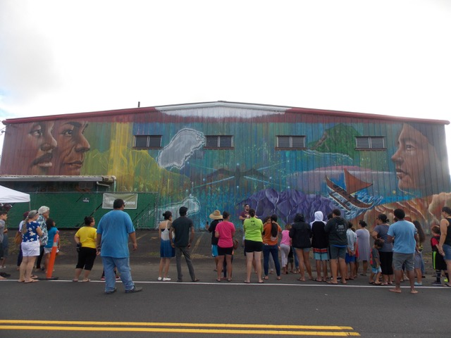 People standing looking at the large mural on side of building. The mural is mostlry greens and blues with two large faces at left and one at right with island and ocean scenes between.