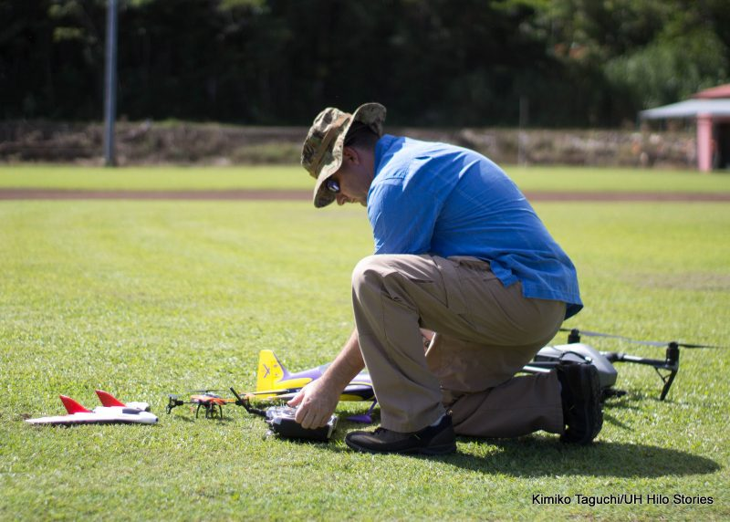 Technician kneeling down on lawn looking over various flying equipment and a drone laid out in front of him. Watermark: the photo was taken by Kimiko Taguchi for UH Hilo Stories.