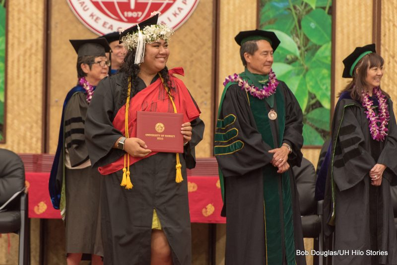 Candidate on dais with diploma.