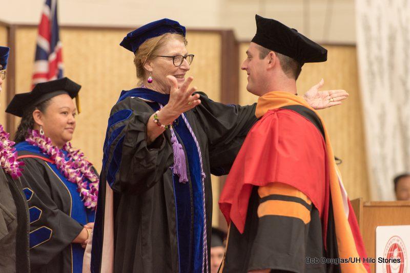 Doctoral degree recipient on dais.