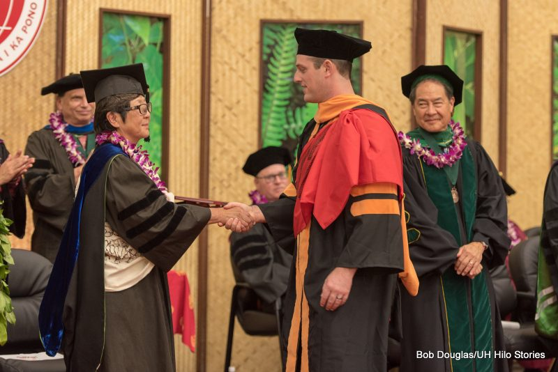 Interim Chancellor shakes hands with candidate.