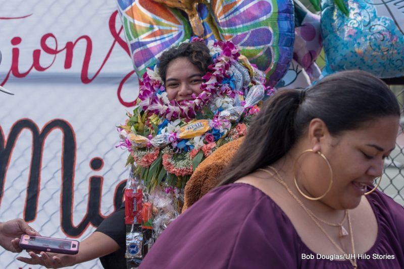 Graduate with lei up to her chin.