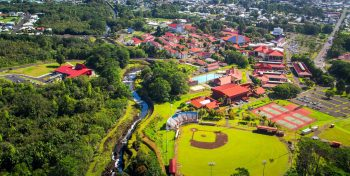 Aerial of campus, red roofs, stream running though, Hilo Bay in background.