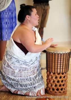 Woman beating on drum.
