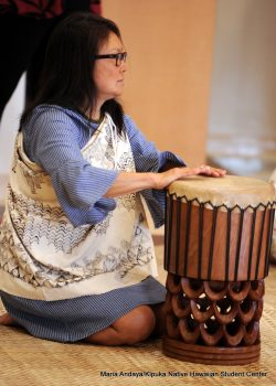 Woman in blue beating on drum.