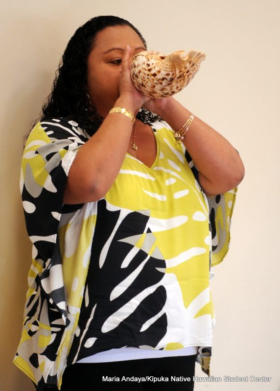 Farrah Marie Gomes blows conch shell.