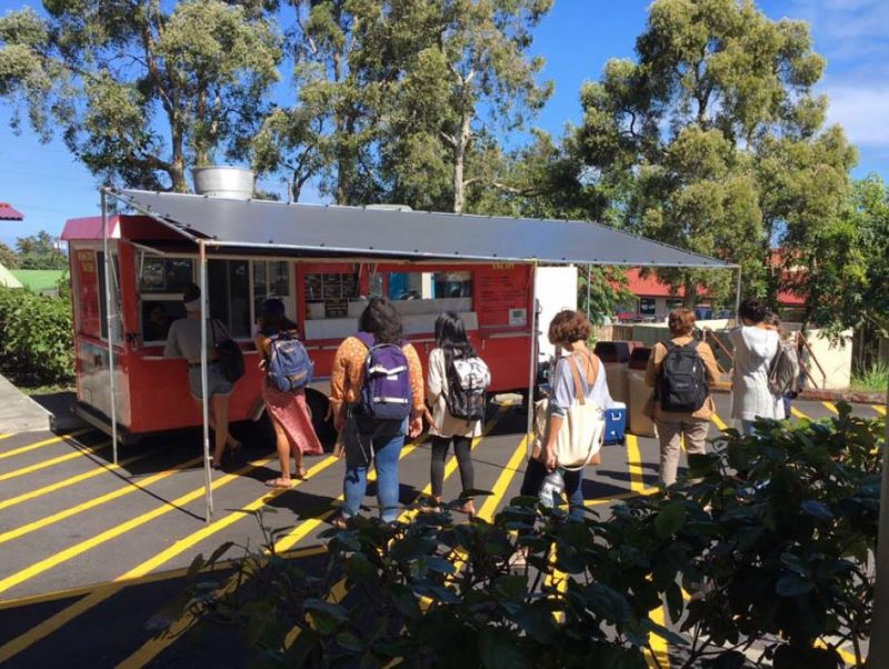 Students line up outside red truck to order food.