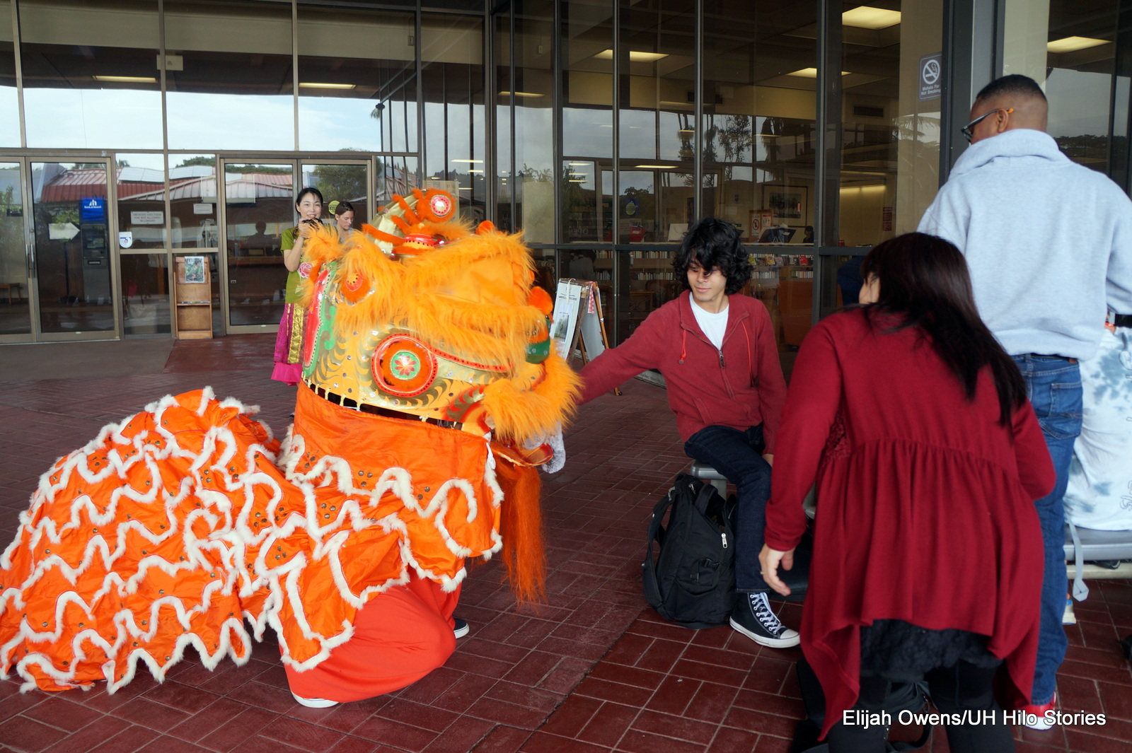 Student places hand in the mouth of colorful orange and red lion.