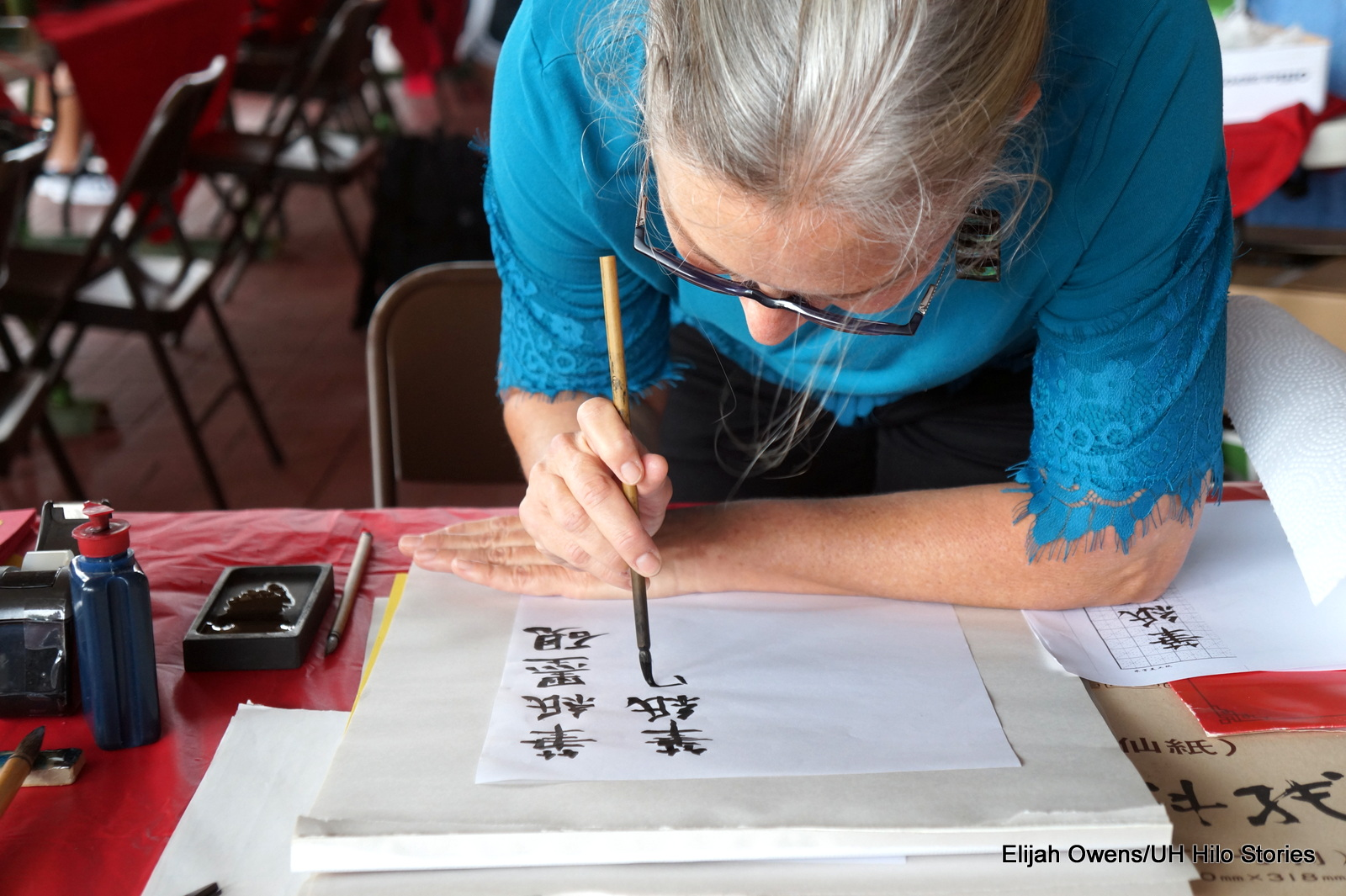 Artists bending over paper to do Chinese calligraphy.