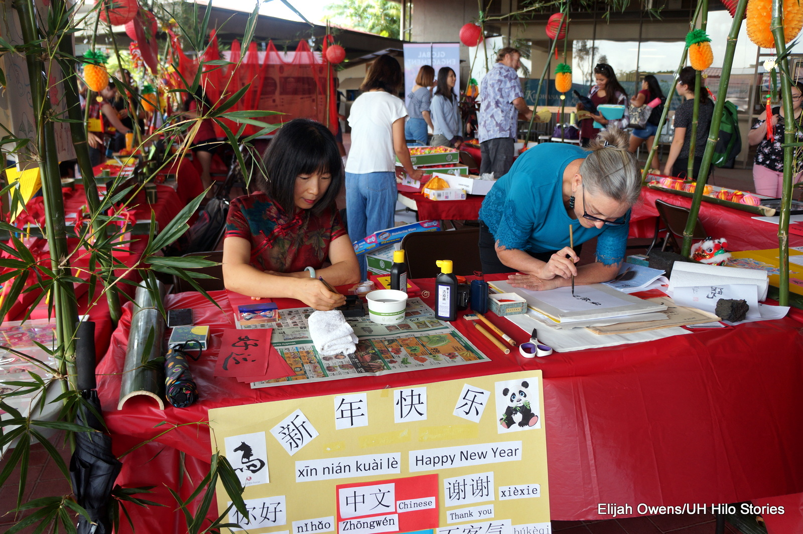 Two women at table doing calligraphy.