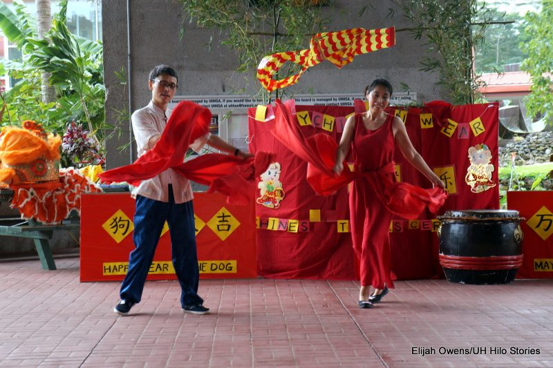 Couple dancing with red silk scarves flowing around them.