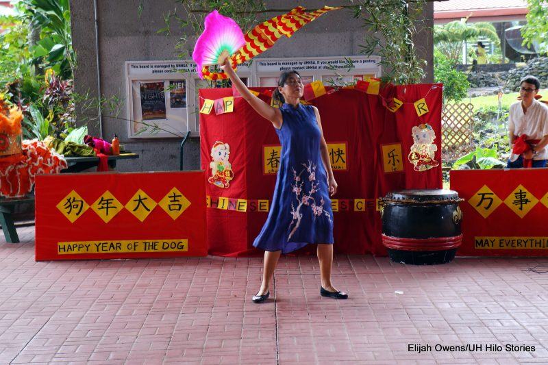 Woman doing fan dance with fan lifted high above her head..