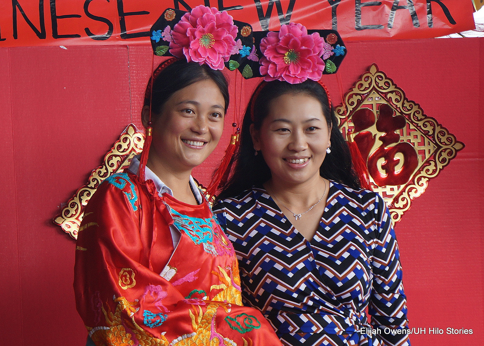 Two women in traditional Chinese attire, bright pink flower on the top of each of their heads. Red background.