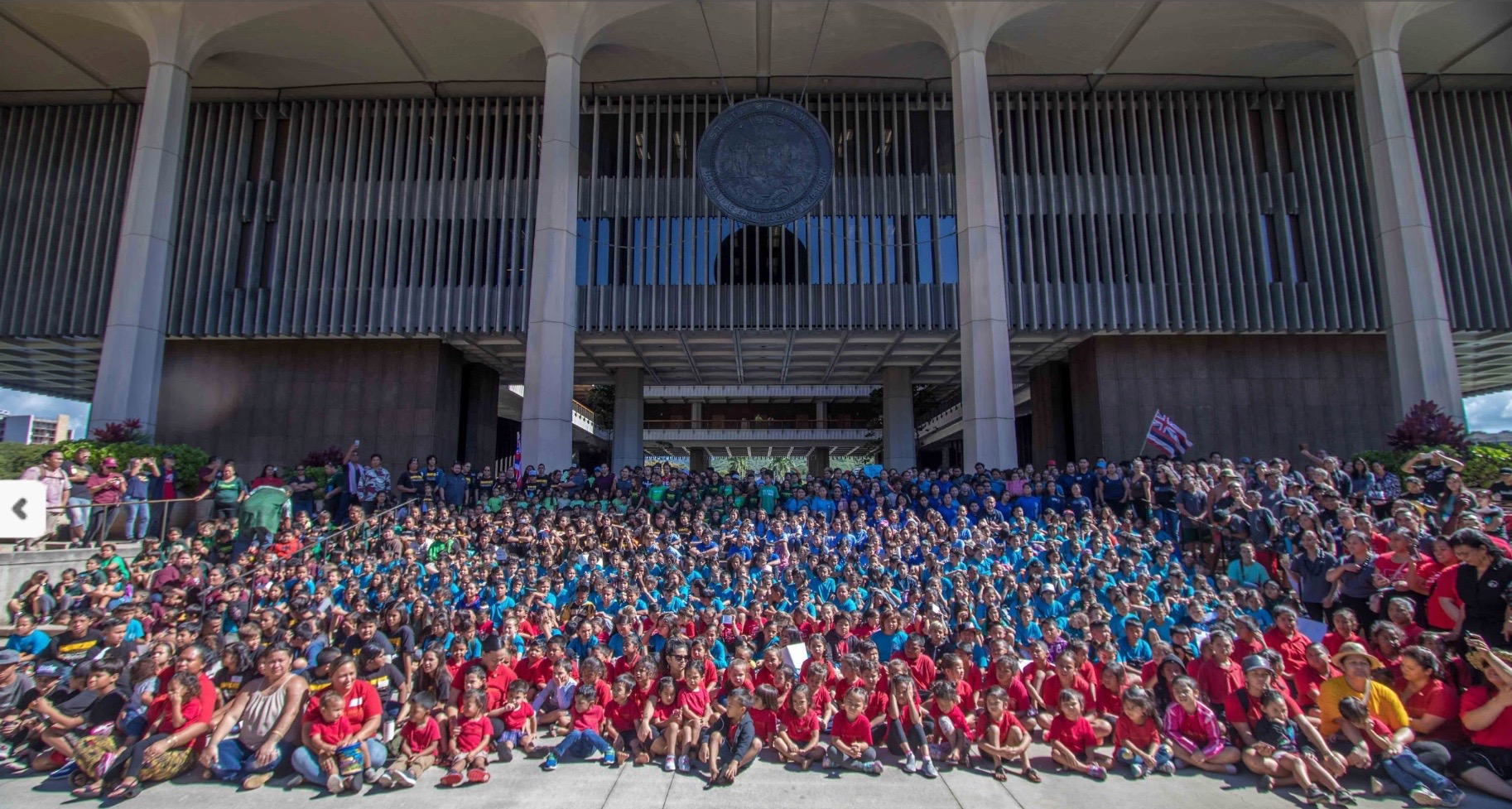 A couple of hundred children on the steps of the capitol sit for photo. The children in front wear red shorts, the rest are in blue. Someone holds the state flag.
