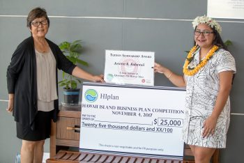 Juvette stands with Chancellor Marcia Sakai and a big oversized check of the prize.