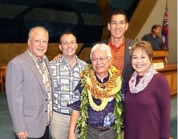 Larry Kimura, Russell Ruderman, Josh Green, Lorraine Inouye, and Kai Kahele stand for a photo on the Senate floor. Larry wears several lei. State flag in background..