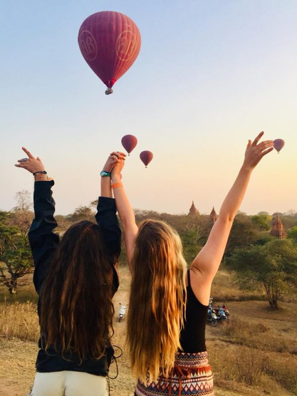 Lindsay Johnson and friend with arms in the air with large hot air balloons rising in background.