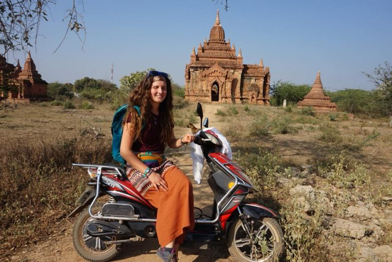 Lindsay on a moped with temple in the background.