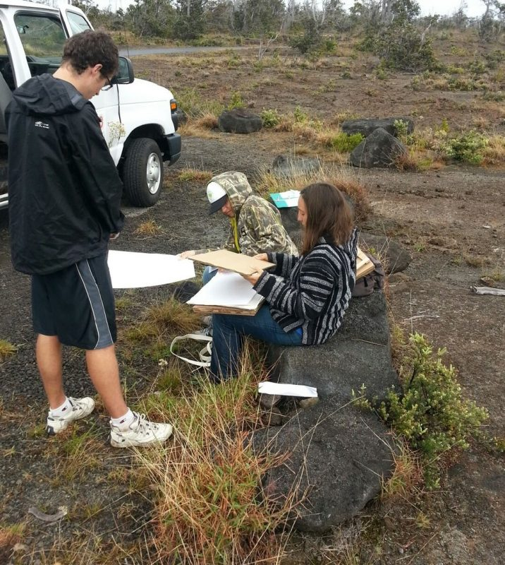 Three students working on specimens in the field. They have notebooks and clip boards.