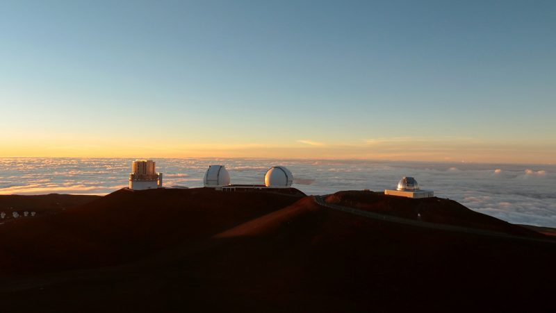 Observatories on summit, above the clouds, at sunset.