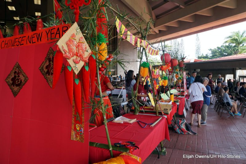 A view of the display tables, lots of red fabrics and paper, dangling Chinese lanterns.