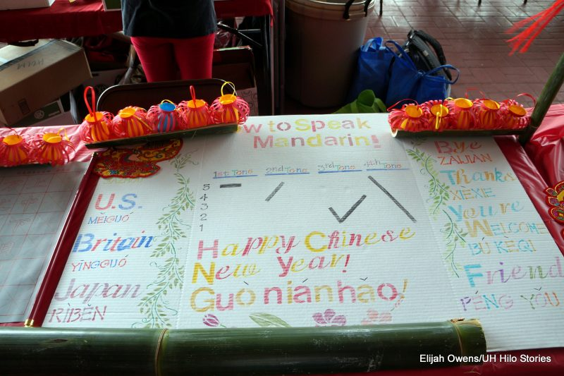 Greetings in different languages are written on a large paper covering a display table.