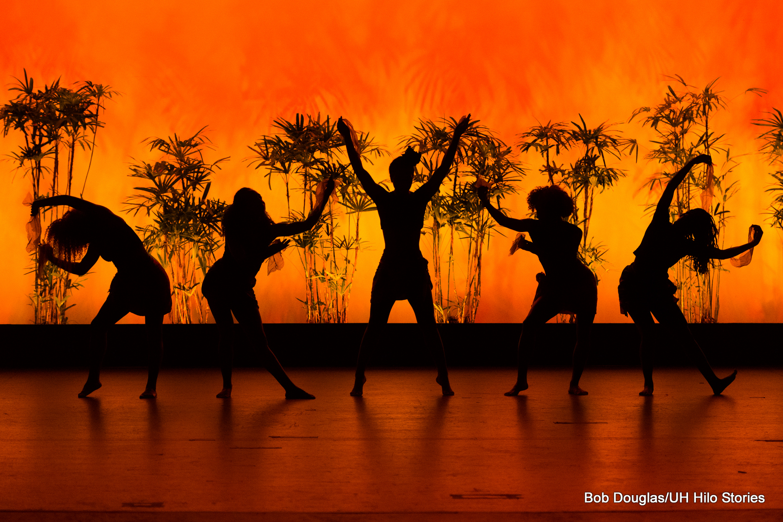Black silhouettes of dancers. against orange lighting.