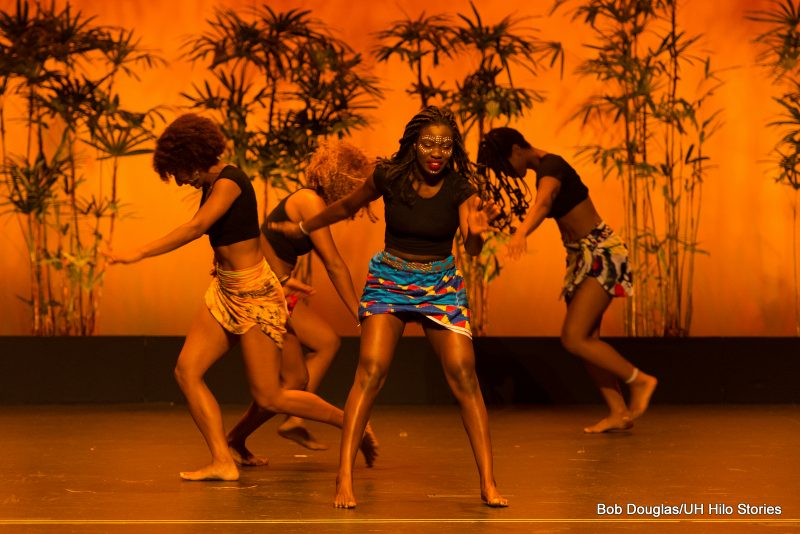 Female dancers in short, ethnic print wraps.