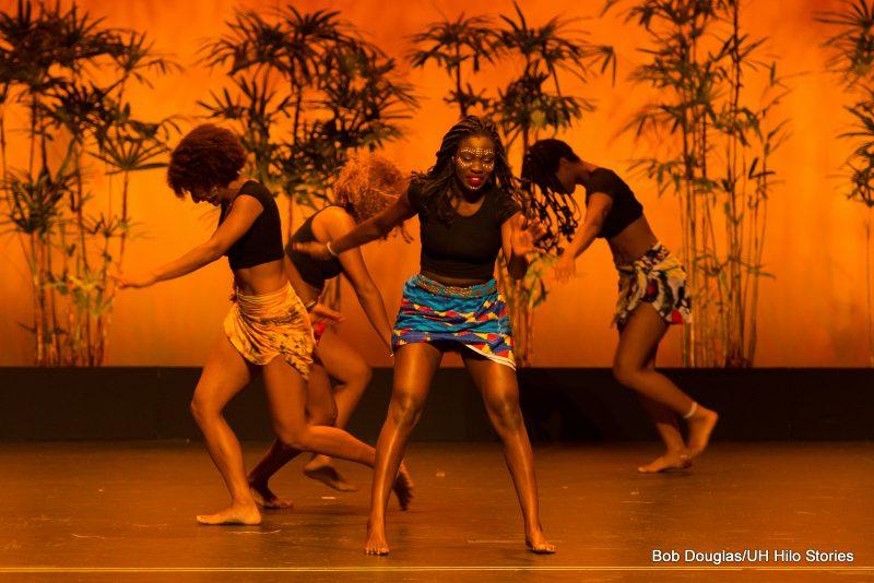 Female dancers in short, ethnic print wraps.