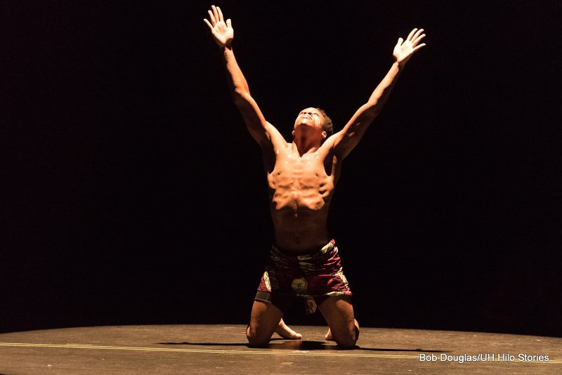 Male dancer on knees. arms outstretched upward to sky, dark lighting.