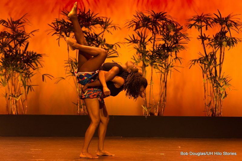 Two women dancers doing an athletic move, one holding the other up off the ground, back to back.