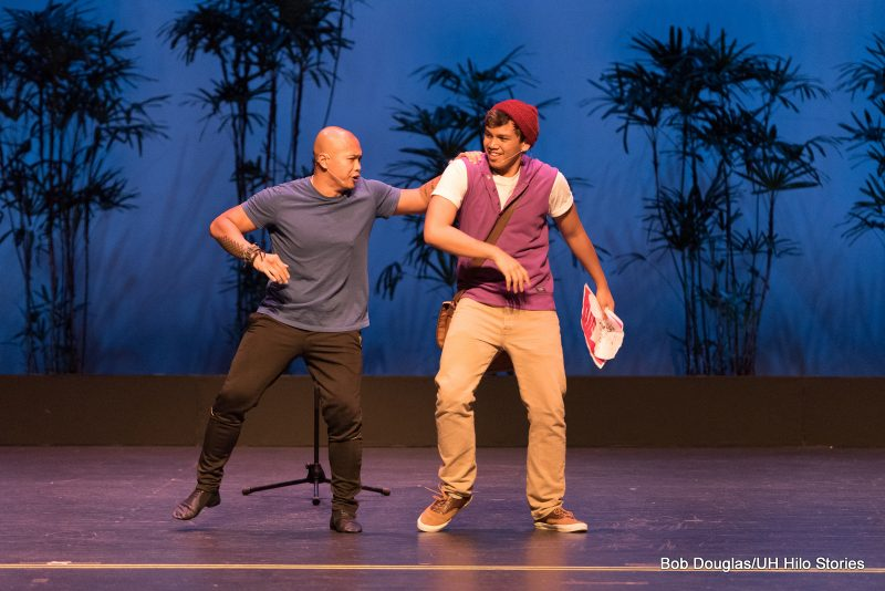 Two males on stage, casual modern dress.