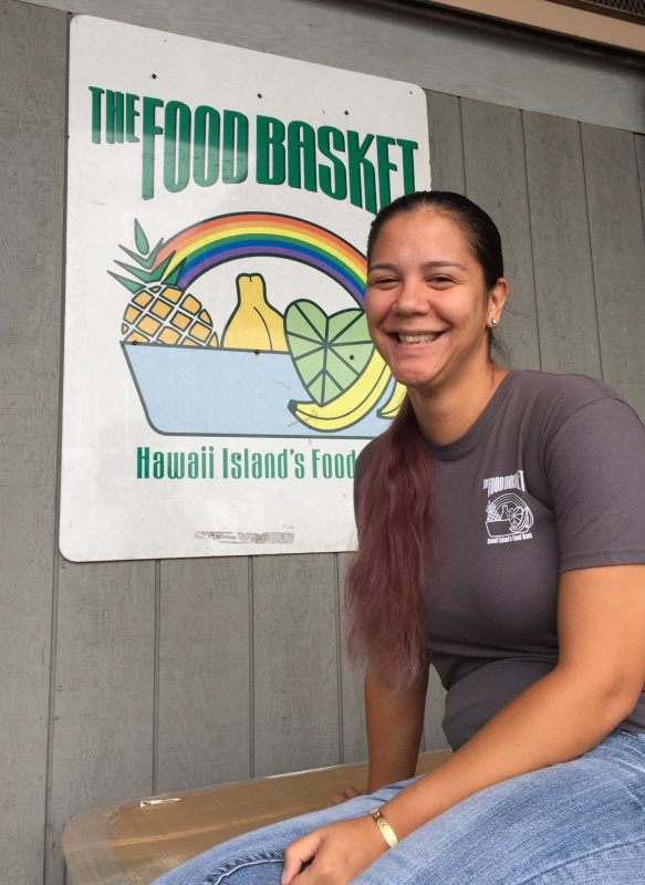 """Haunani seated next to sign on the front of building: """"THE FOOD BASKET. Hawaii Island's Food...."""" Graphic design of a basket of fruit."""