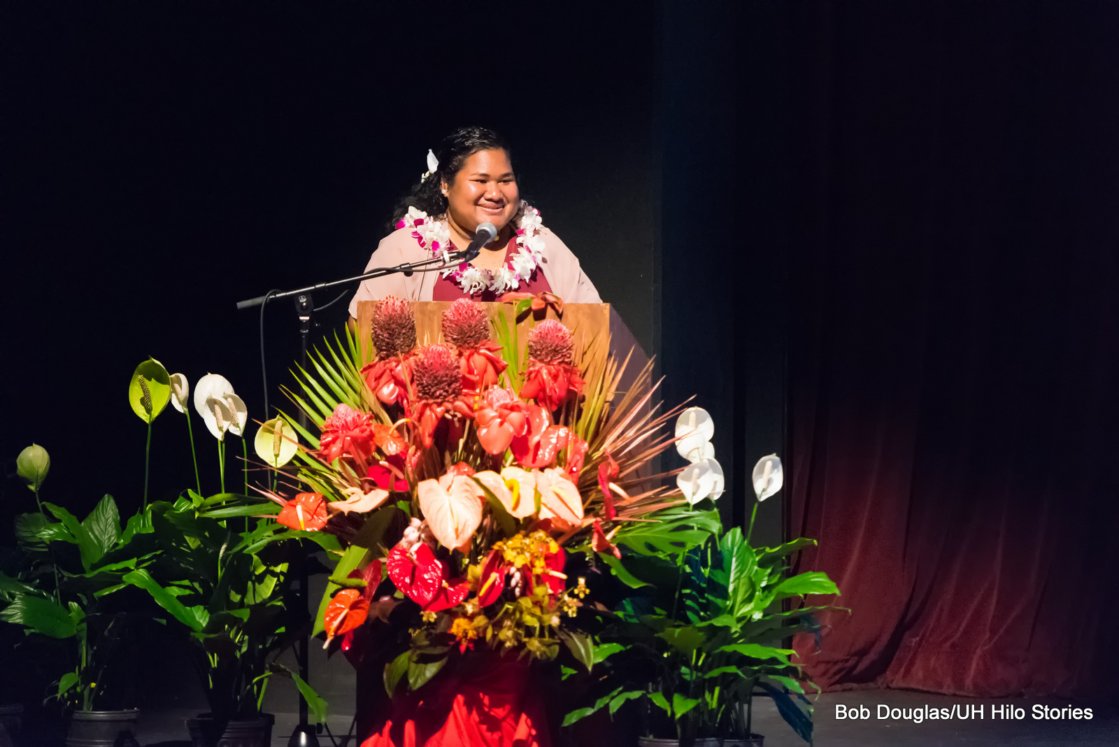 Woman at podium, at mic. Large floral arrangement in front of podium.