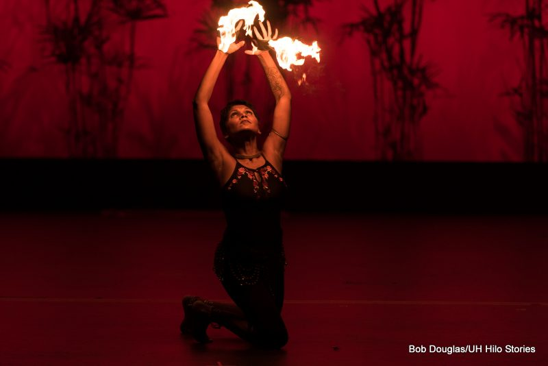 Female dancer kneeling, with flames shooting from her hands.