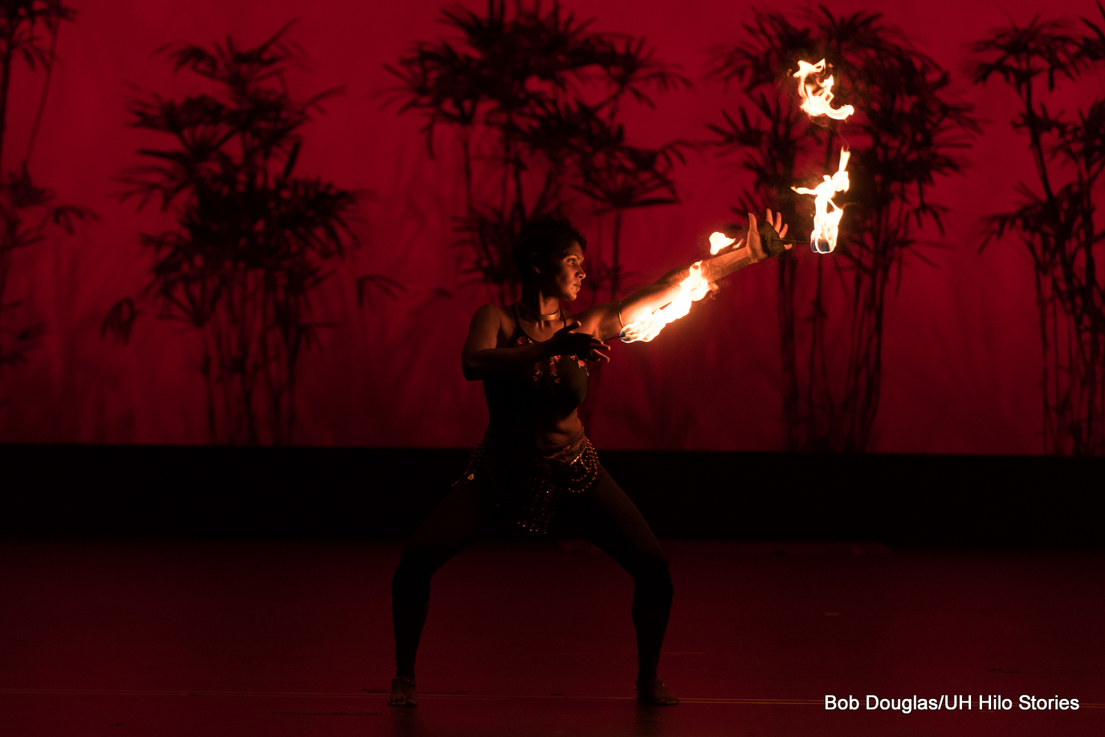 Woman dancer with flames coming off her hands. Dark red lighting in background.