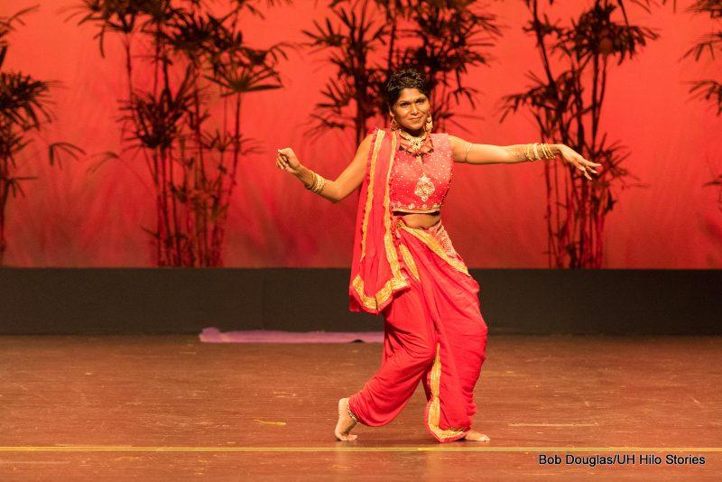 Woman in orange sari doing dance with arm gestures.